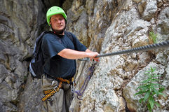Young man climbing on via ferrata Stock Photo