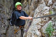 Young man climbing on via ferrata Stock Photo
