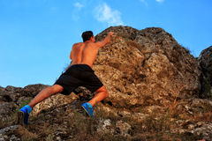 Young man climbing on a wall. With blue sky on the background Stock Images