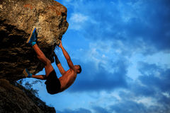 Young man climbing on a wall. With blue sky on the background Stock Photos