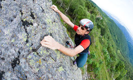 Young man climbing on a wall with green valley on the background Royalty Free Stock Images