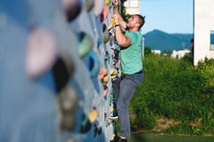 Young man climbing wall rock outdoors Stock Images
