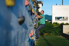 Young man climbing wall rock outdoors Royalty Free Stock Photos
