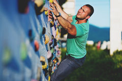Young man climbing wall rock outdoors Stock Photo