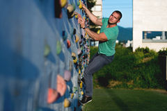 Young man climbing wall rock outdoors Stock Photos