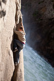 Young man climbing beside waterfall Royalty Free Stock Photography