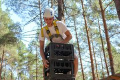 Young Man Climbs High Extreme middle. Extreme games entertainment sports in the forest, a young man in helmet and with insurance is climbing on high pyramid of stock photo