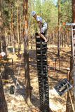 Young Man Climbs High Extreme wide. Extreme games entertainment sports in the forest, a young man in helmet and with insurance is frightened and climbing on high Stock Photography
