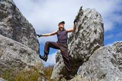 Young man climbs on rock. Low angle, against sky. Shot in Hottentots-Holland Mountains nature reserve, near Grabouw, Western Cape, South Africa Royalty Free Stock Photos