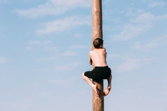 Young man climbs on a wooden post on the traditional holiday dedicated to the approach of spring - Slavic celebration Royalty Free Stock Photo