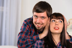 Young man close ears his girlfriend. Couple portrait Stock Photography