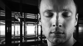 Young man with closed eyes in dark interior Stock Photography