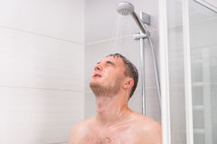 Young man with closed eyes taking a shower in the bathroom. Young man with closed eyes taking a shower, standing under flowing water in shower cabin with Royalty Free Stock Photography