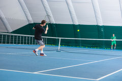 The young man in a closed tennis court with ball. The young fit man in a closed tennis court with ball and racket Stock Photo