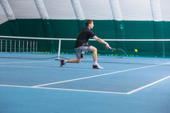 The young man in a closed tennis court with ball. The young fit man in a closed tennis court with ball and racket Stock Photography