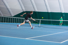 The young man in a closed tennis court with ball. The young fit man in a closed tennis court with ball and racket Royalty Free Stock Photography
