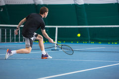 The young man in a closed tennis court with ball. The young fit man in a closed tennis court with ball and racket Royalty Free Stock Photo