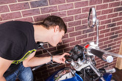 Young Man Closely Examining Gauges on Motorcycle Stock Photo