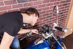 Young Man Closely Examining Gauges on Motorcycle Royalty Free Stock Image