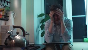 Young man closes computer sitting at kitchen while kettle boiling on stove stock footage