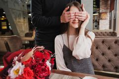 A young man closes his eyes to the girl, his wife, and gives a bouquet of red flowers in a cafe by the window. royalty free stock image