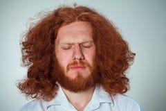The young man closing both eyes. The young man with long red hair closing both eyes Royalty Free Stock Images