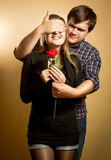 Young man closing girlfriends eyes and giving her red rose Royalty Free Stock Image
