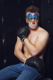 Young man in clown makeup. In the studio on a black background royalty free stock photography
