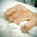Young man clutching tightly his pillow in bed. Closeup of the hand of a young caucasian man clutching tightly his pillow in bed stock photos
