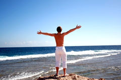 Young man on coast the sea. Having lifted hands towards to freedom Royalty Free Stock Photos