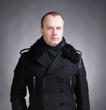 Young man in coat. Portrait of young handsome man wearing winter coat and scarf on a gray background Stock Image