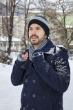 Young man in a coat covered with snow Royalty Free Stock Photo