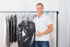 Young man with coat in dry cleaning store. Young Happy Man Standing With Coat In Dry Cleaning Store Stock Photos