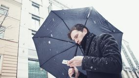 Young man in coat with umbrella under snowfall using smartphone on alley. Young man in coat and knitted scarf with black umbrella under snowfall using a stock video