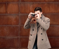The young man in a coat photographs model the vintage camera at a metal rusty wall Royalty Free Stock Image