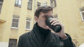Young man in coat standing under snowfall drinking coffee from black plastic cup. Young man in gray coat in knitted scarf standing under snowfall drinking coffee stock video
