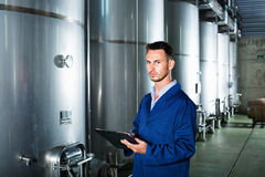 Young man in coat taking notes on wine factory Stock Photography