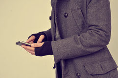 Young man in coat using a smartphone Stock Image