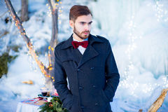 The young man in a coat in the winter. The young man in a coat with a stylish hairdress and with a red butterfly poses near an ice floe in the winter Stock Photo