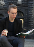 Young man with coffee reading book in old center of europe city Royalty Free Stock Photos