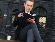 Young man with coffee reading book in old center of europe city Stock Image