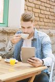 Young man in coffee shop cafe using a tablet. Stock Photo