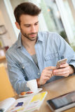 Young man in a coffee shop on his smartphone Stock Images