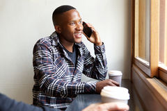 Young man at a coffee shop talking on mobile phone Stock Photo