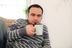 Young man with coffee or tea. Young man at his home holding a mug with coffee or tea Stock Photography