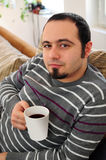 Young man with coffee or tea. Young man at his home couch holding a mug with coffee or tea Stock Photo