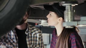 A young man, a colleague, shares his experience with a beautiful girl, a new employee of a service station, how to. Repair a car. A man and a woman under the stock video