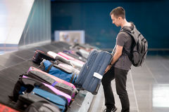 Young man collecting his luggage Stock Images