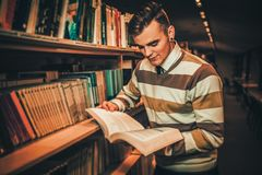 Young man in a college library royalty free stock image