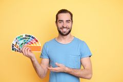 Young man with color palette. On yellow background stock images